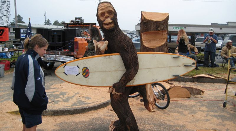 Chainsaw carving of Sasquatch with a surfboard.